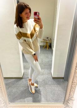 Witte skinny jeans met beige pull en sneaker met print